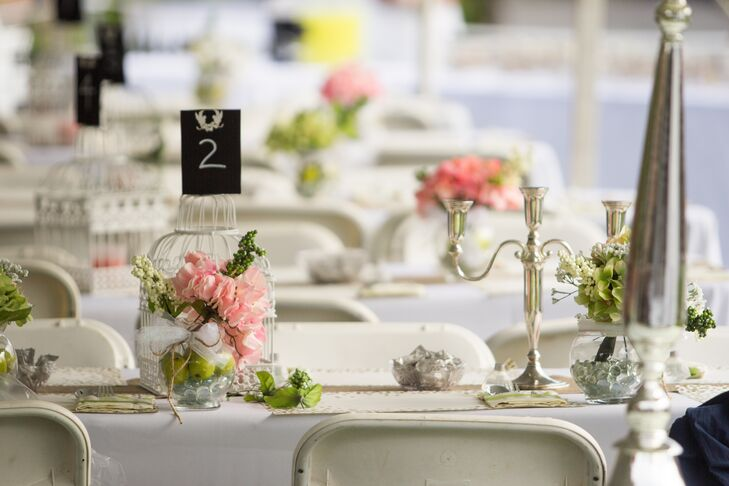 The reception tables were decorated with pink hydrangeas and berries in glass vases filled with pebbles and fresh fruit. Wanting to add a little romance to the space, they also had silver candelabras and birdcages to hold the table numbers.
