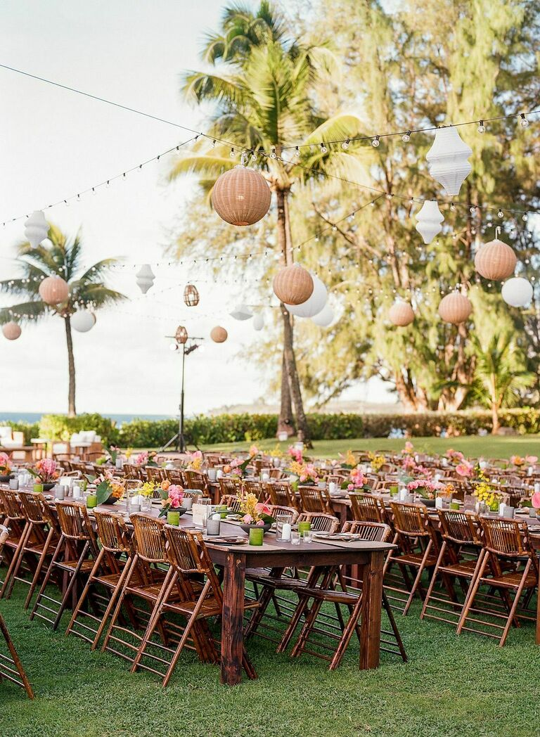 Beach reception with wood tables, bamboo folding chairs and woven chandeliers