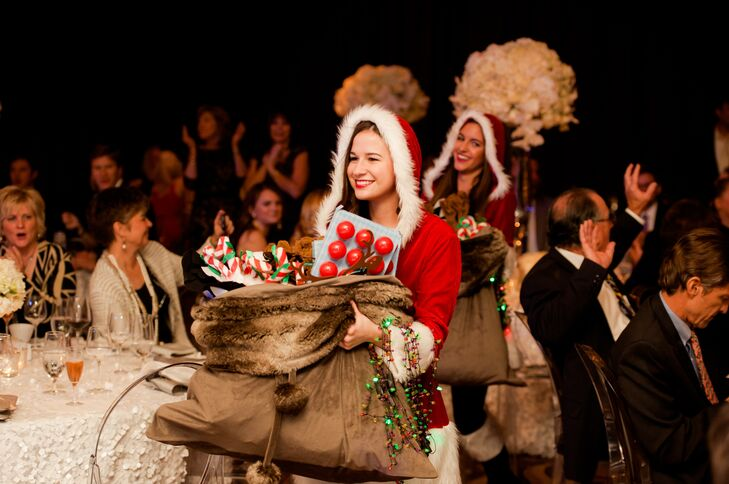 """As Dance Street Band played """"All I Want For Christmas Is You,"""" Santa's helpers popped into the reception with bags of Christmas-themed apparel for guests to wear before a grand entrance by Santa Claus."""