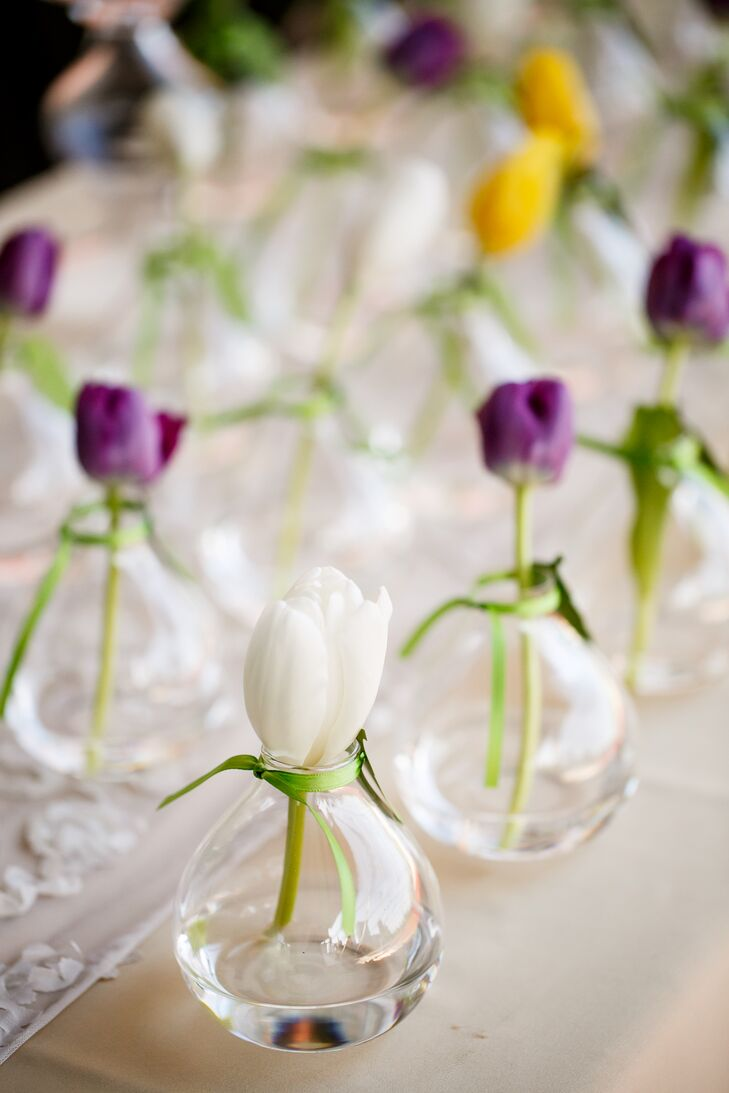"The couple gifted guests with bud vases from CB2. ""They were cute and fit in perfectly with our garden party theme,"" the bride says. ""They also worked out perfectly because we used them to display our escort cards as a leaf-shaped attachment with tulips."""