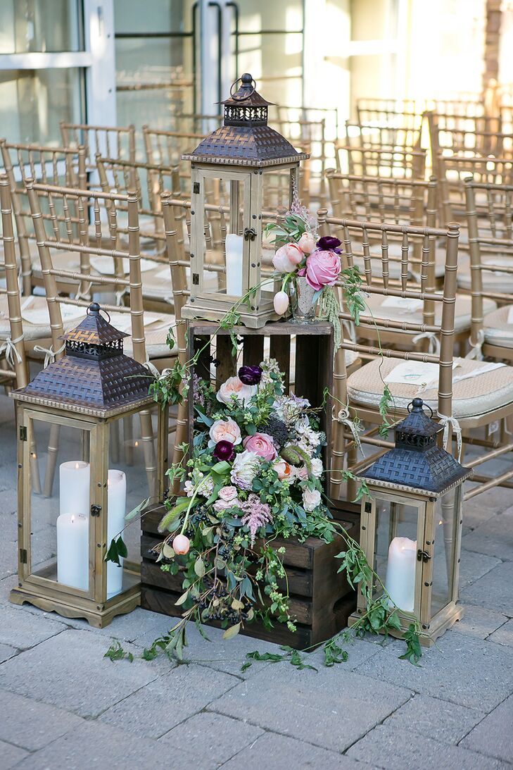 Arrangements of wooden lanterns with candles and wooden crates overflowing with greens, white, pink and blush roses marked the entryway to the ceremony at Stone House at Stirling Ridge in Warren, New Jersey.