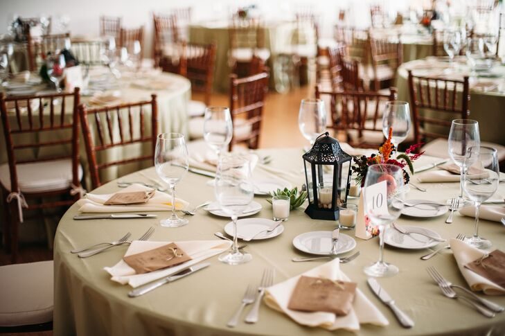The reception dining tables were dressed in green linens with ivory napkins and had a garden lantern on each table filled with earth colored stones and a candle.