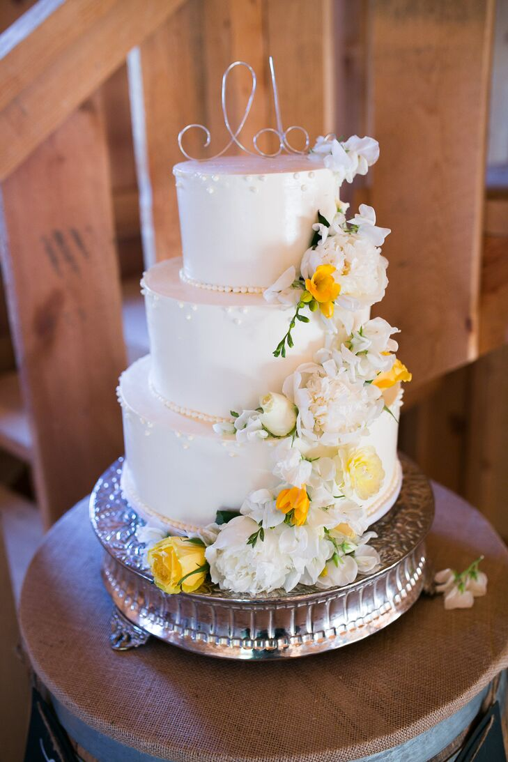 Fresh white and yellow flowers scaled the three-tier white wedding cake from top to bottom, propped up on top of an elegant silver stand. The entire sweet display embodied the white, yellow and silver color scheme seen throughout the celebration.