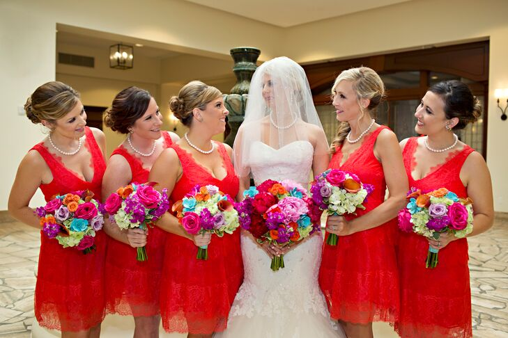 Jess's bridesmaids wore red lace dresses by BCBG Bridal with an elegant updo and pearls.
