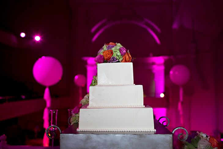 Baked by Bittersweet Confections, the couple chose a three-tiered white wedding cake with colorful roses and hydrangea cascading along each tier.