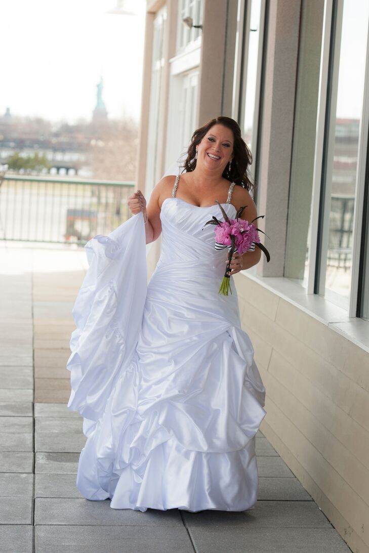 """""""I wanted my dress to be simple and elegant,"""" Emily says. She wore a white satin dress with bunching and custom-designed beaded straps."""
