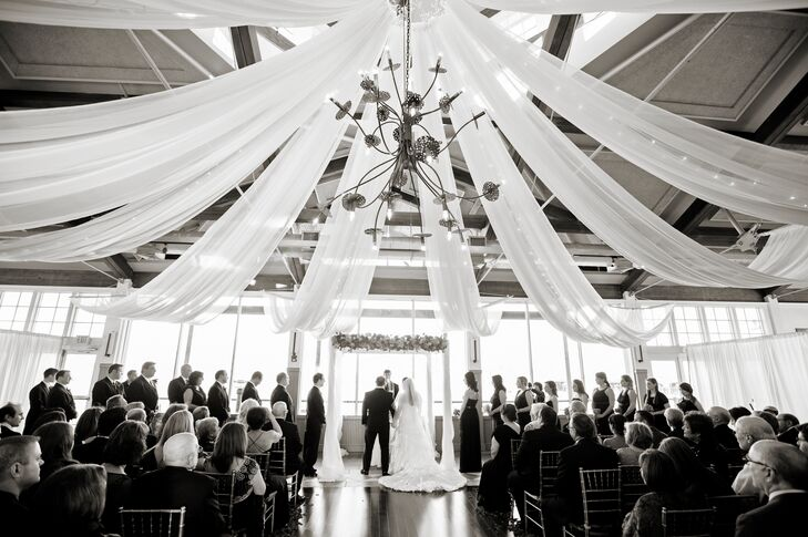 White drapery and a chandelier created and elegant look to Emily and Corey's wedding ceremony at the Liberty House Restaurant.