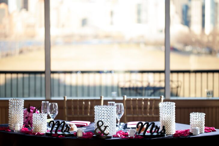 Emily and Corey's sweetheart table was decorated with pink rose petals and glass candle holders.