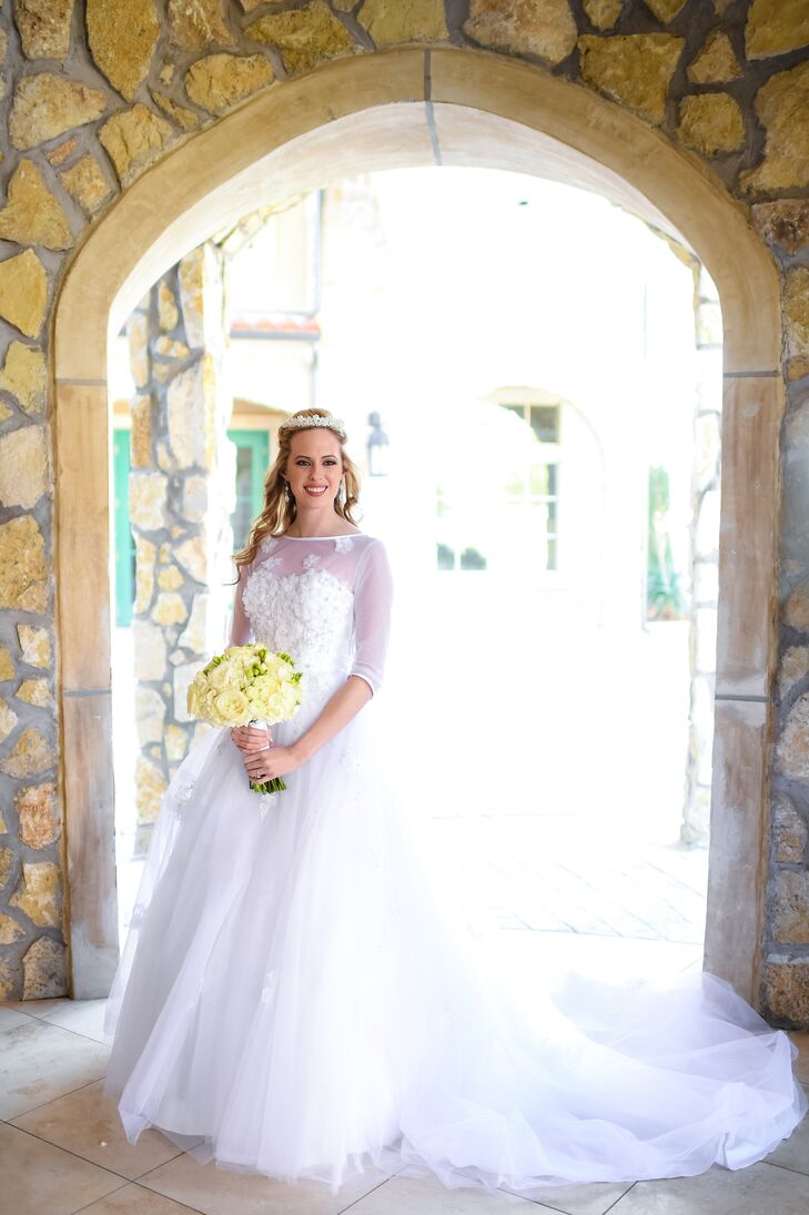 Courtney wore an Alfred Angelo ball gown with lace details and a full tulle skirt and train. The dress also featured an illusion neckline and sheer three-quarter sleeves that created a romantic effect.