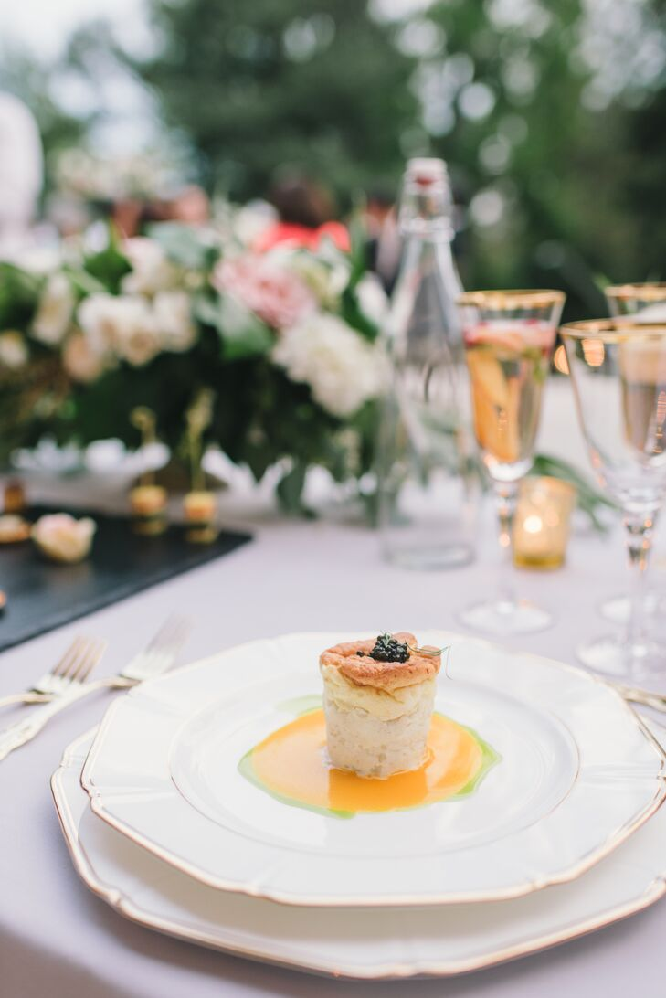 A seafood-centric menu by Le Papillon was served on light gray linen-covered tables set with gold-­accented ivory china, elegant gold flatware and gold­-rimmed glassware. Atop each place setting sat a peach napkin and a dinner menu with dusty blue font.