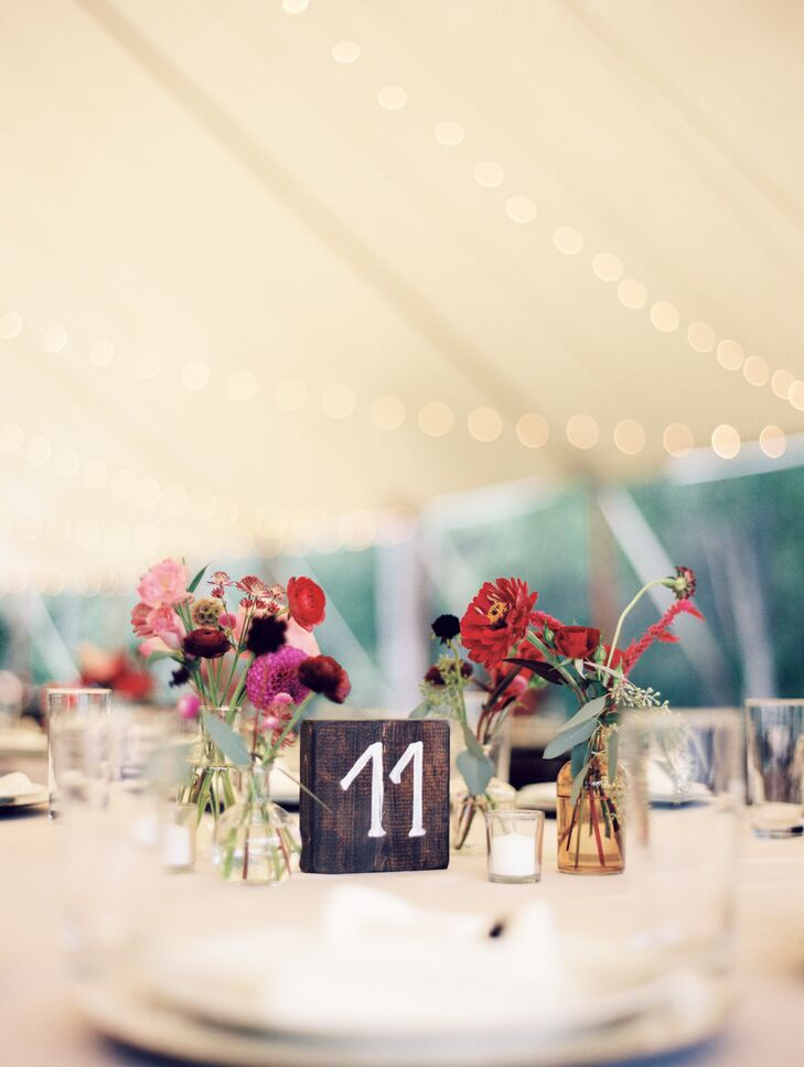 To capture the wedding's free-spirited feel, Moonstone & Moss filled vintage-inspired bud vases with small bouquets of seasonal blooms in shades of red, purple and pink. The petite bundles were offset by eucalyptus accents that gave the centerpieces a fresh scent and a cool contrast.