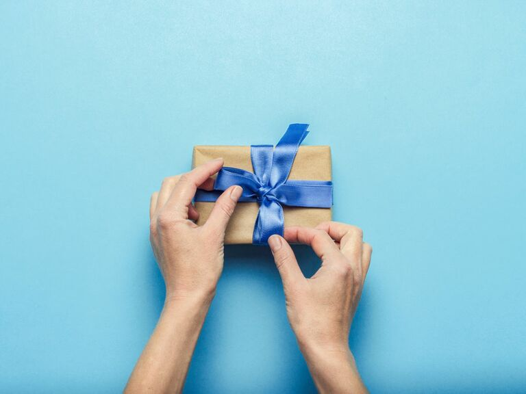 Wedding guest wrapping gift with blue bow