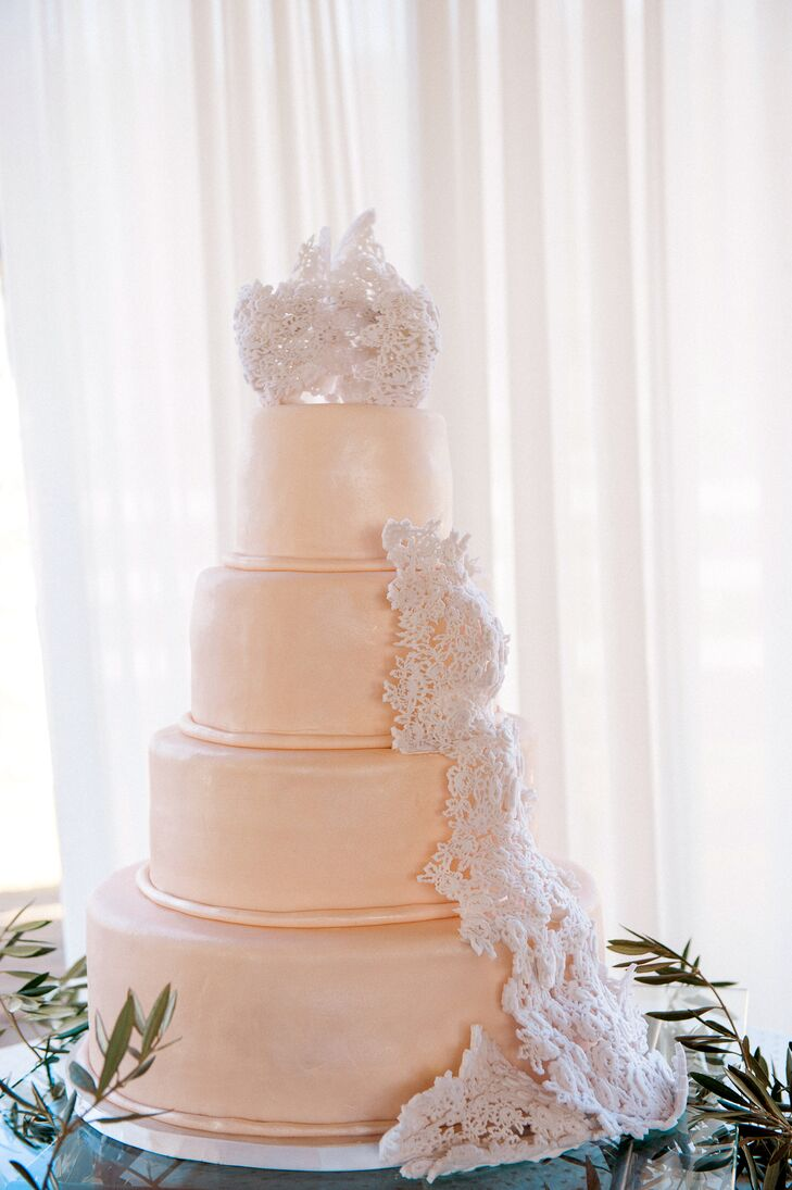 The four-tier classic wedding cake had no additional decor besides sugar lace that trailed down the sides and sat on top of the dessert. Alyssa's wedding dress lace overlay served as the inspiration behind the lace accents on the cake.