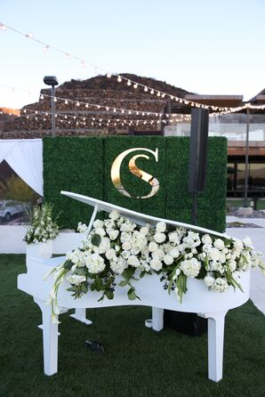 Classic Piano with White Roses in front of a Greenery Wall with a Gold Monogram
