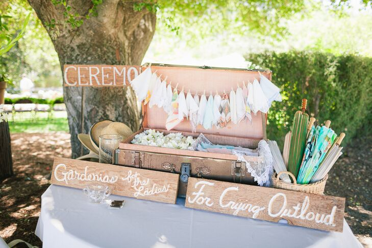 There was a table set up at the ceremony that supplied guests with everything they needed at the outdoor occasion. A leather vintage trunk was opened and displayed a line of hanging handkerchiefs, and the trunk was half-filled with gardenia flowers to throw during the recessional while the other half was filled with more handkerchiefs. Hats and parasols were available for guests to use during the sunny summer day.