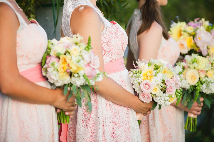 The bridesmaids wore white lace wedding dresses lined with various shades of pink, and they wore a sash in a matching color that was wrapped around the waist. Their pastel bouquets were filled with hydrangeas, roses, lilies and peonies accented with veronica .