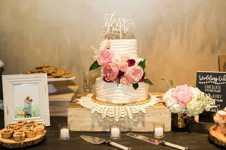 """The three-tier cake featured a """"Love You More"""" cake topper."""
