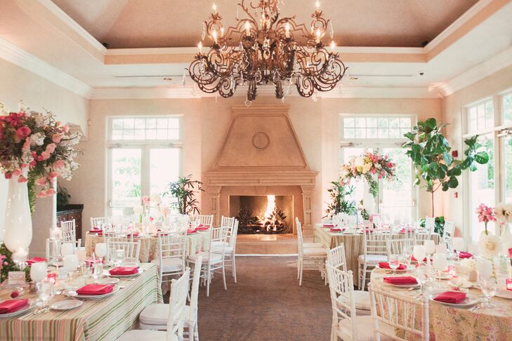 The reception took place inside the Spanish Hills Country Club in Camarillo, California. The space was entirely bordered with large windows, letting natural light in, and included the glow of the elegant bronze chandeliers and lit fireplace. Dining tables were dressed in striped or floral tablecloths, and set with hot pink napkins on top of white dinnerware.