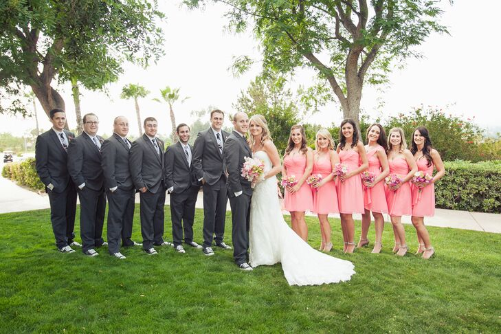 "The couple stood in the middle of their wedding party, dressed in pink coral dresses and dark gray suits. ""The bridesmaids all wore a different style of dress but had the same coral color,"" the couple says. ""This let them each have their own style, which was perfect. The boys wore tuxes from Friar and black Converse sneakers for a fun kick."""