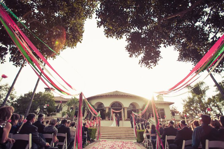 "Megan and Jared were married at the top of the steps outside at Spanish Hills Country Club in Camarillo, California. The aisle was lined with colorful ribbon and had scattered rose petals leading to the altar. ""We visited a lot of potential locations for the venue, but couldn't find the right one until we got to Spanish Hills,"" the couple says. ""We chose it because they have beautiful grounds with flourishing flowers and trees, along with a spectacular room for the main event."""