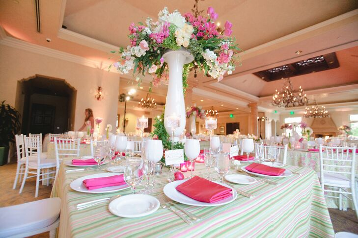 The pink-, white- and green-striped tablecloth dressed the square dining table, set with white dinnerware and pink napkins. The middle of the table was decorated with a tall white vase filled with a lush arrangement of roses, tulips and stock. The reception took place inside the venue at  Spanish Hills Country Club in Camarillo, California.