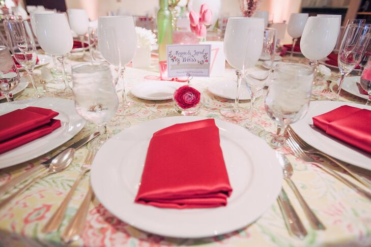 The dining table dressed in a floral tablecloth was set with white dinnerware and pink napkins. A photo holder with a crystal paperweight at the bottom was decorated with a pink ranunculus, had a thank-you card clipped at the top for guests who attended the wedding.
