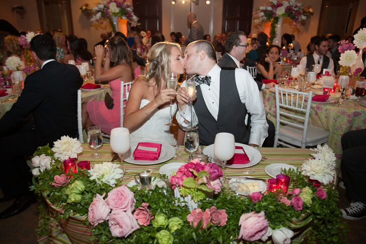Megan and Jared shared a kissed while they were seated at the sweetheart table during their reception, which took place inside at Spanish Hills Country Club in Camarillo, California. Their table was set with white dinnerware and bright pink napkins, with a lush floral garland filled with roses and chrysanthemums decorating the head.