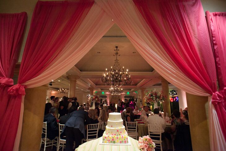A four-tiered wedding cake was served at the reception, which was decorated with yellow, pink and green sugar flowers toward the bottom. It was displayed on a table underneath pink draped linens, opening up into the reception lit by elegant chandeliers.