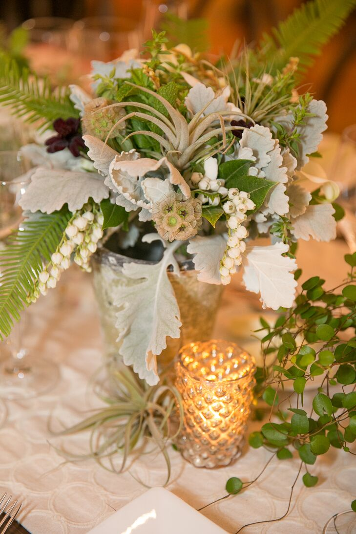 Lilies of the valley, scabiosa pods, dusty miller and a mix of leafy greens made up the centerpieces that decorated dining tables at the reception. Candles placed inside glass holders added a romantic glow.