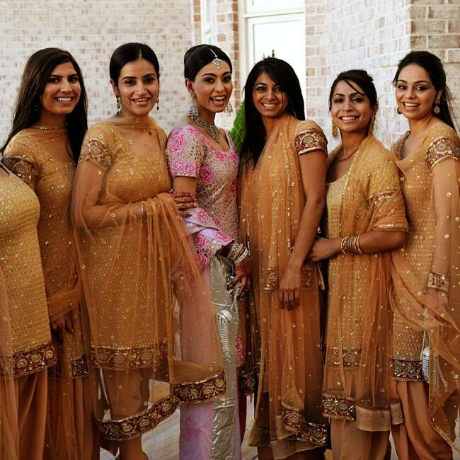 Dolci's bridesmaids wore traditional Salwar Kameez gowns and sheer dupatta, long scarves, during the ceremony. The peach, gold and red trimmed fabric complemented the pink shades in Dolci's gown and the ceremony décor.