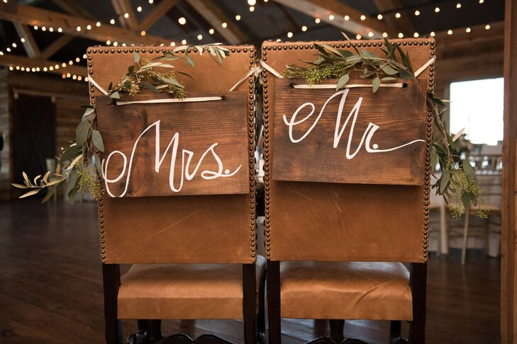 Green vines and hand-painted rustic wooden signs adorned the backs of the bride's and groom's chairs at the reception. The warm brown leather was the perfect touch under the exposed wooden beams and worn wooden floors of the venue.