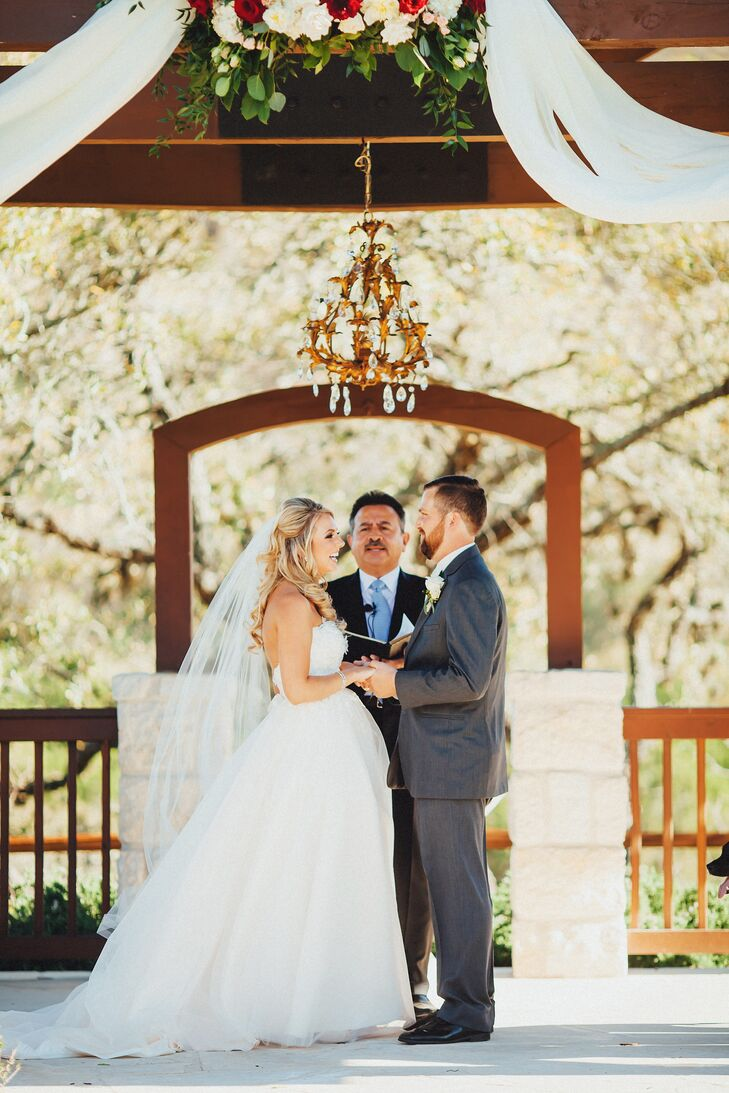 To tie the rustic venue together with elegant touches, white fabric was draped through the wooden gazebo rafters and fell along the sides. A large floral arrangement decorated the center, accented by a gold chandelier, which hung above Courtney and Andrew as they recited their vows.