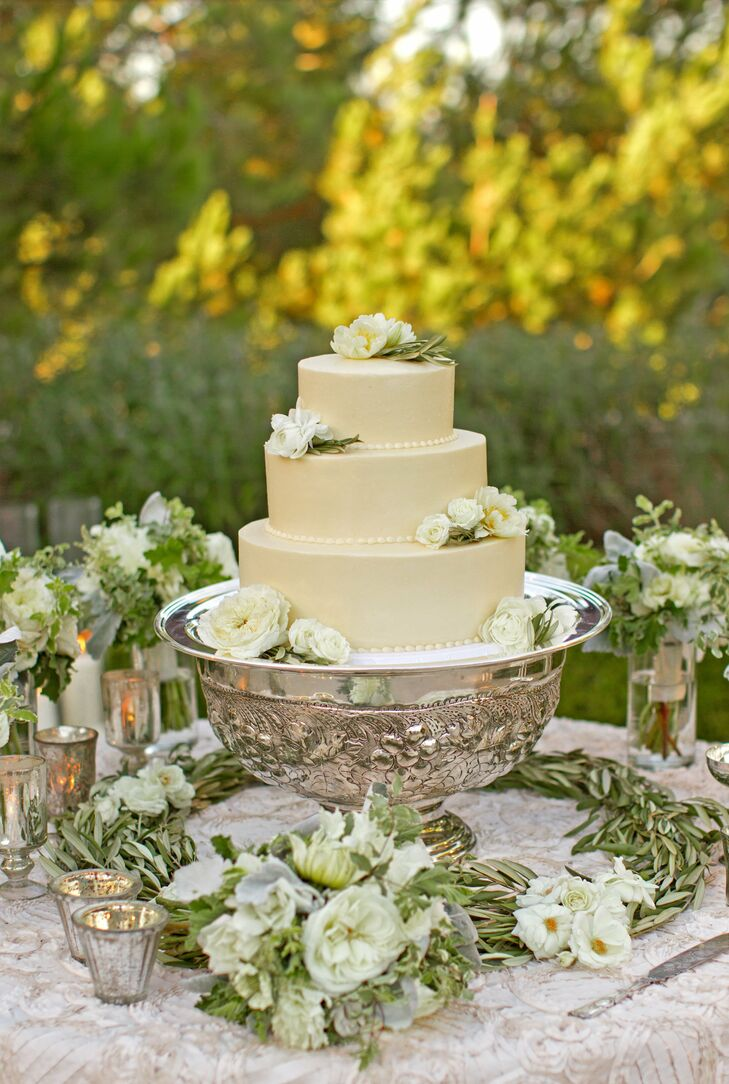 The three-tier cake was decorated with champagne-colored buttercream frosting, buttercream pearls and cascading ivory blooms.