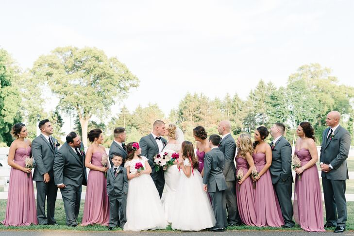 While the bridesmaids dressed from head-to-toe in romantic mauve looks, the groomsmen suited up in more conservative outfits. They donned formal charcoal tuxedos from the Black by Vera Wang collection at Men's Wearhouse. The darker hue provided a welcome, dapper contrast against the bridesmaids. Steve stood out among them with a black bow tie. Sara, however, matched her flower girls with a chic white dress and off-the-shoulder sleeves.