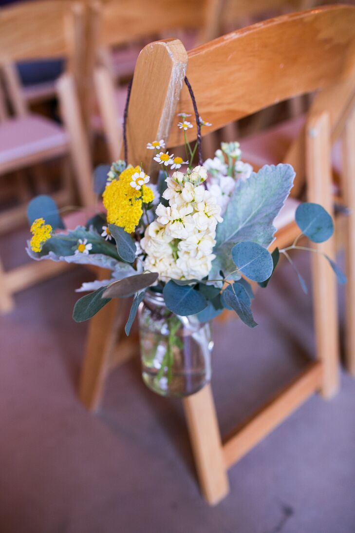 Lauren walked down the aisle lined with hanging glass vases, filled with white and yellow flowers. She and her bridesmaids matched the decorations with their bouquets incorporating similar colors and blooms.