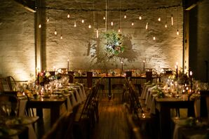 Industrial Reception Space with String Lights and Flower Installation