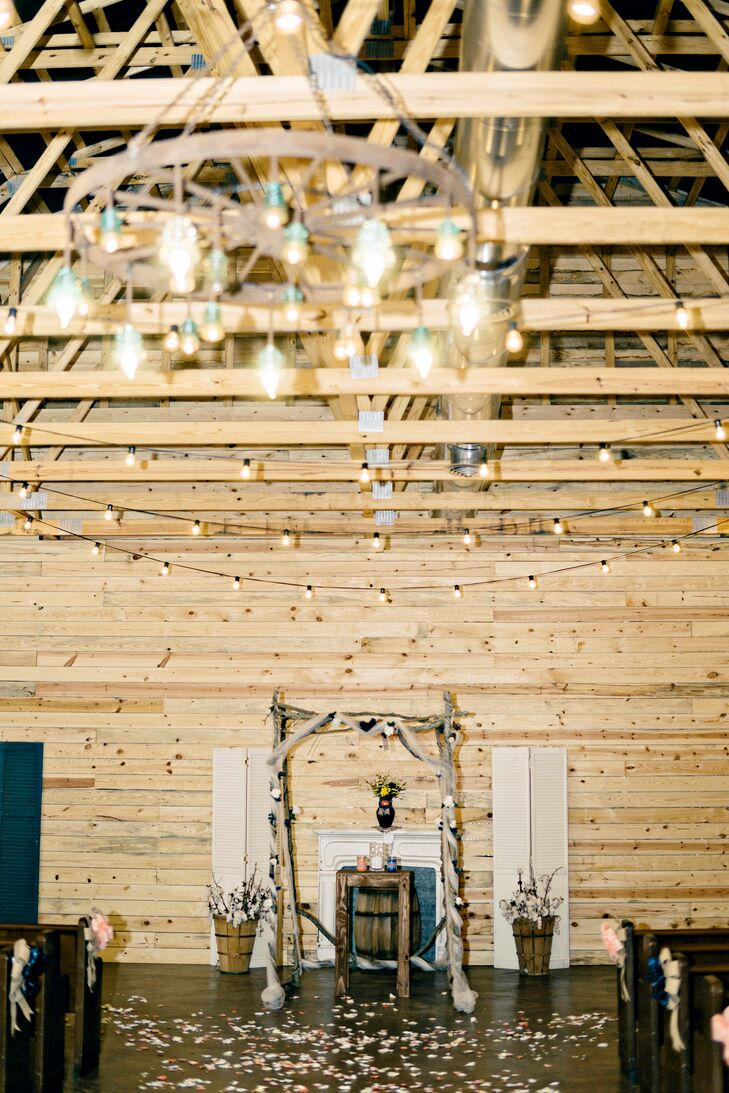 "Chris built their branch wedding arch, along with the table where he and Samantha participated in the sand-pouring unity tradition. They said ""I do"" in this rustic wooden barn, illuminated by string lights and a chandelier."