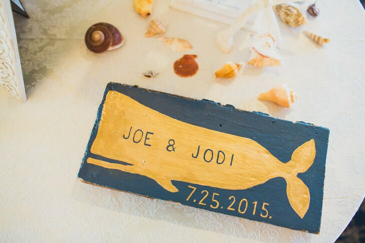 Nothing says nautical like a few sea-worthy accents. To decorate their table of family photos, Jodi and Joe surrounded it with seashells, white lanterns and a sign. Their names and wedding date were painted on the gold whale, creating a standout keepsake.