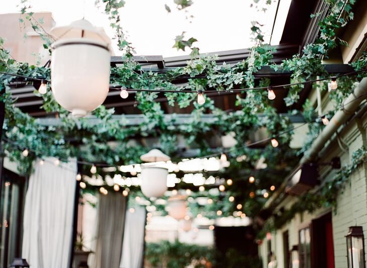 A canopy of ivy and bistro lights hung over the long banquet tables, illuminating the rooftop terrace in a warm, romantic glow. The simple touch, paired with the bundles of burgundy blooms that dotted the reception tables, brought the couple's secret-garden vision to life.