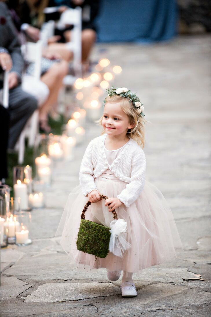 A blush dress with full tulle skirt, floral crown and a moss basket gave the flower girl a whimsical look.