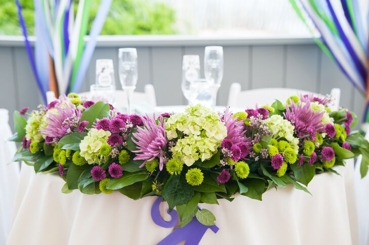 The sweetheart table was decorated with a flower arrangement of purple and green chrysanthemums, viburnum and leafy greens.