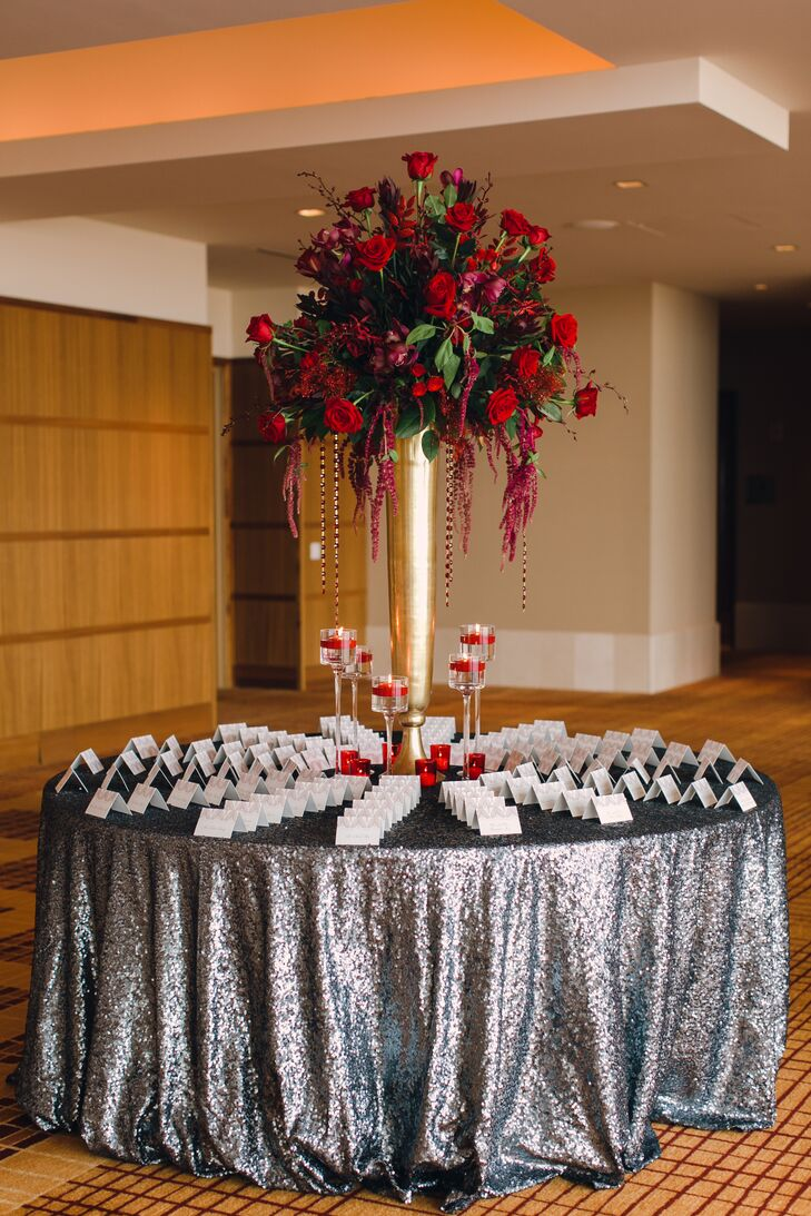 Guests found their table assignments at a glamorous round table, complete with a sparkly silver linen and vertical arrangement of red roses.