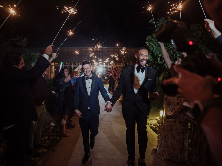 Grooms leaving wedding reception with sparkler exit