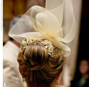 Five porcelain flower pins, borrowed from her sister, accented Maggie's chic updo. Topping off her look was an ivory mesh nylon hat pinned at an angle.