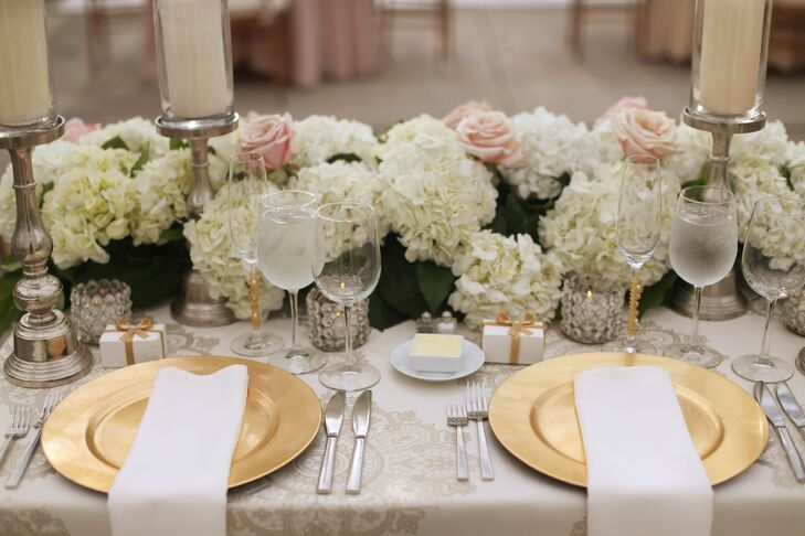 Dinnerware included gold chargers paired with silver flatware. The sweetheart table centerpiece featured a long arrangement of white hydrangeas, blush roses and greenery. Ivory pillar candles covered in glass were interspersed, while votives in crystal-beaded cups accented the arrangements.