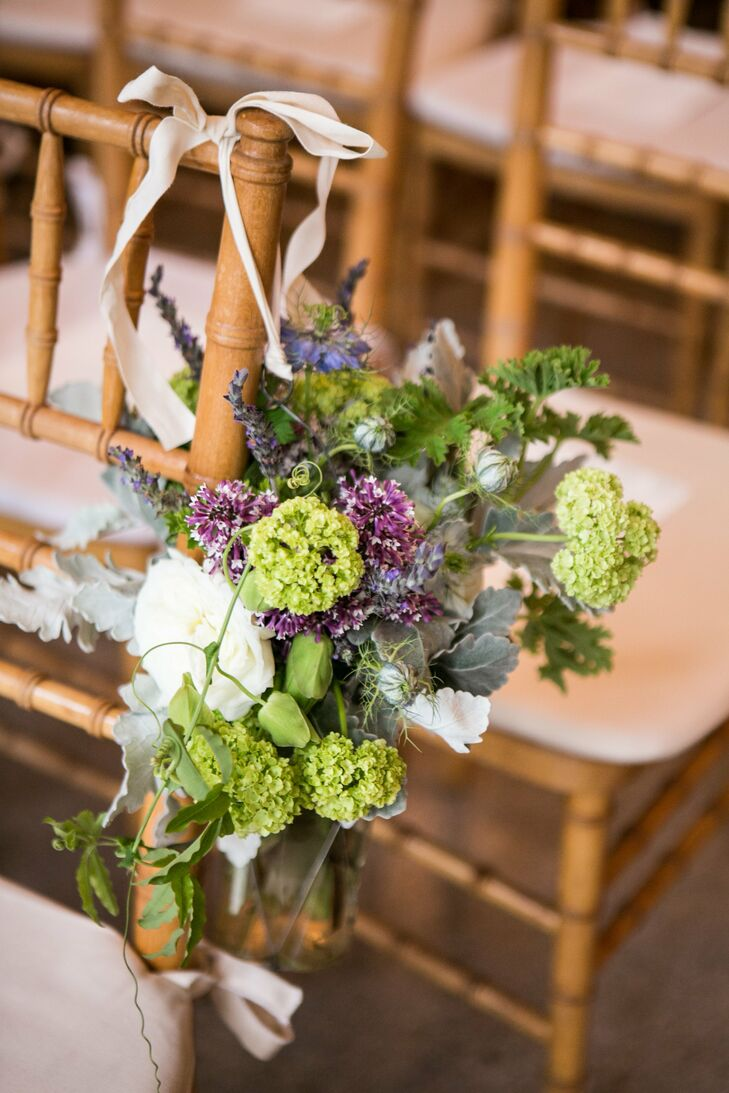 Clusters of garden roses, hydrangeas and dusty miller hung from the chiavari chairs flanking the indoor aisle.