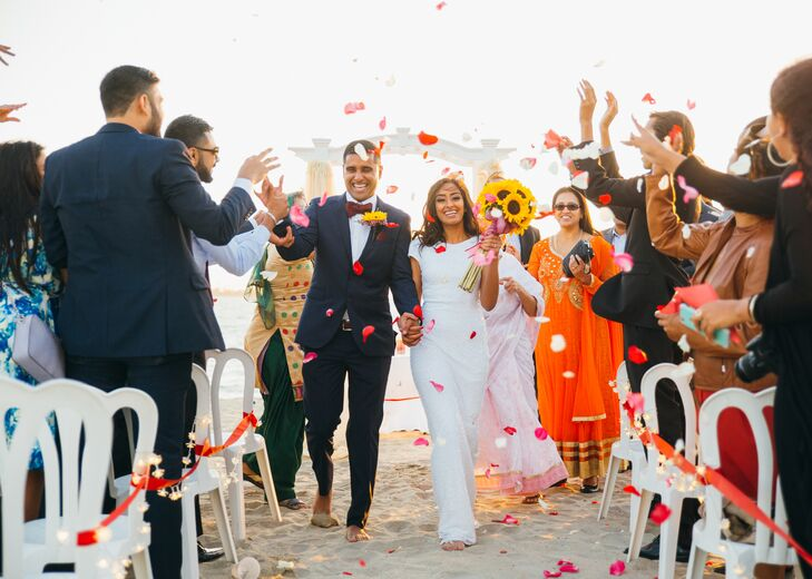 Guests tossed red and pink flower petals in the air as Vidya and Pinder took their first sandy steps (barefoot, of course) as husband and wife.