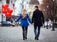 couple walking down street with heart balloons