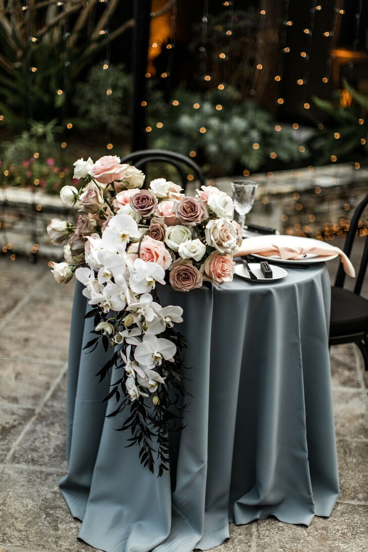 Sweetheart Table With Blue Linen and Dramatic Floral Arrangement