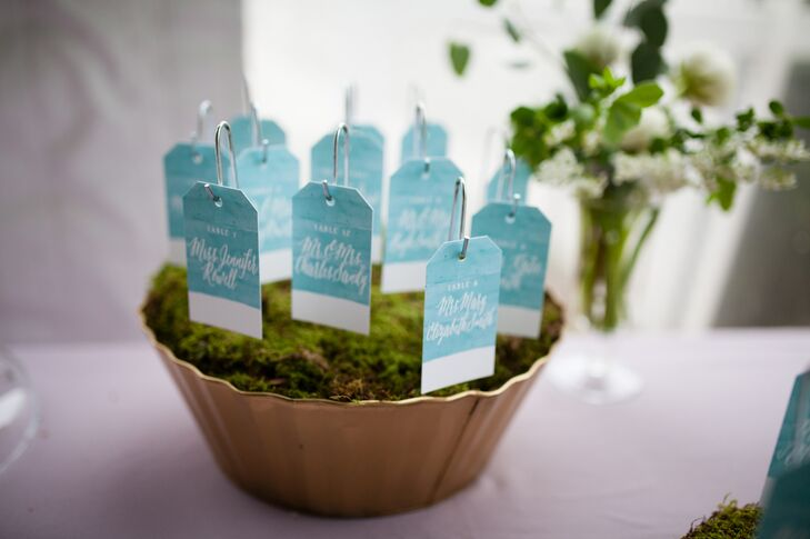 A garden-inspired theme ran throughout the decor, with Sebesta Design decorating the tables with opulent arrangements of white full blooms and cascading greenery and mossy escort card displays leading guests to their seats. Designer Jessica Stalnaker of Empress Stationery designed the whimsical escort cards, painting them with pale blue watercolor paints and hand-lettering the names of the couple's guests in white on each.